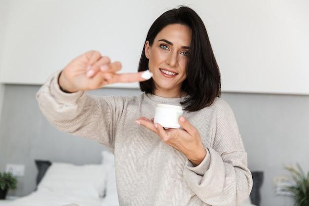 Imagem de uma mulher atraente com 30 anos segurando um frasco com creme facial, em um quarto moderno e bem iluminado