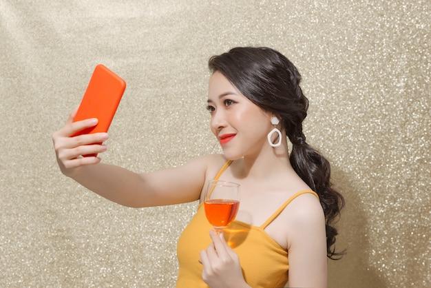 Imagem de uma mulher atraente e bonita segurando a taça de champanhe enquanto tira a foto de selfie isolada na parede de brilhos.