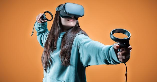Imagem de uma mulher bonita e elegante usando óculos de realidade virtual e segurando joysticks