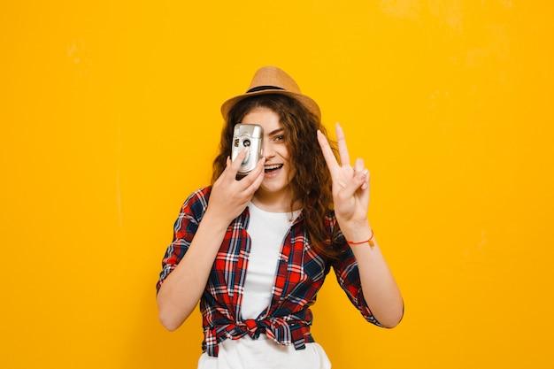 Imagem de uma mulher bonita, tirando uma foto com uma câmera retro e mostrar gestos isolados sobre parede amarela