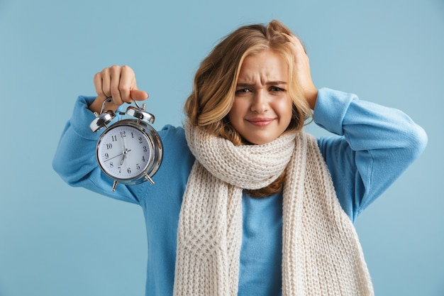 Imagem de uma mulher de 20 anos chateada, enrolada em um lenço, segurando o despertador e segurando a cabeça