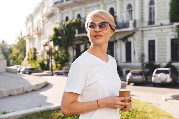 Imagem de uma mulher europeia elegante, na casa dos 30 anos, vestindo camiseta branca e óculos escuros, andando pelas ruas da cidade no verão e bebendo café para viagem em um copo de papel