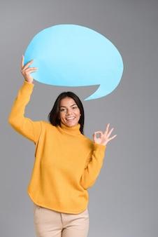 Imagem de uma mulher feliz posando isolada sobre uma parede cinza segurando balão de fala, mostrando o gesto certo.