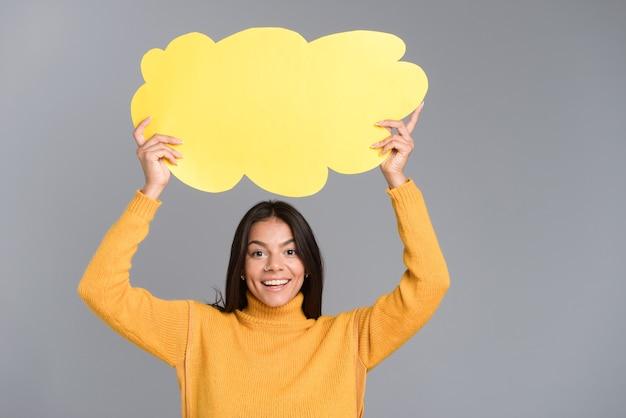 Imagem de uma mulher feliz posando isolada sobre uma parede cinza, segurando o balão de pensamento.