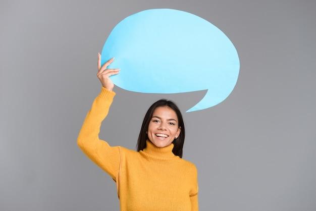 Imagem de uma mulher feliz posando isolada sobre uma parede cinza, segurando um balão de fala.
