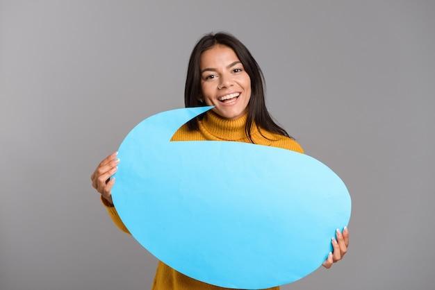 Imagem de uma mulher feliz posando isolada sobre uma parede de parede cinza, segurando um balão de fala.