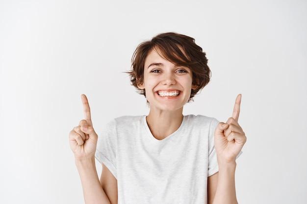 Imagem de uma mulher fofa e animada com um penteado curto e uma pele limpa e brilhante, apontando os dedos para cima e sorrindo para uma parede branca