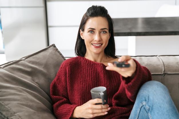 Imagem de uma mulher incrível dentro de casa em casa no sofá assistir tv bebendo café.