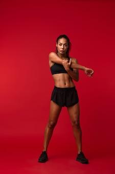 Imagem de uma mulher jovem forte de fitness esportes africanos posando isolado sobre a parede vermelha fazer exercícios.