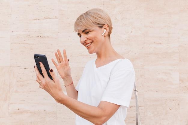 Imagem de uma mulher loira adulta vestindo uma camiseta branca usando telefone celular e fone de ouvido sem fio para videochamada, em pé contra uma parede bege ao ar livre