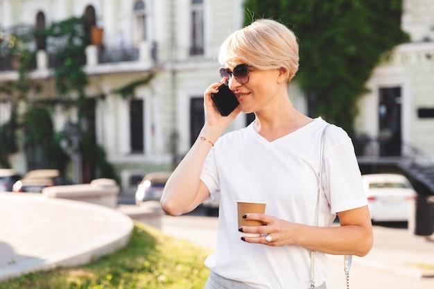 Imagem de uma mulher loira caucasiana usando camiseta branca e óculos escuros, andando pelas ruas da cidade no verão com café para viagem e falando no celular