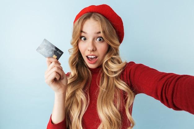 Imagem de uma mulher loira de 20 anos, alegre, usando uma boina vermelha, segurando um cartão de crédito enquanto tirava uma selfie isolada