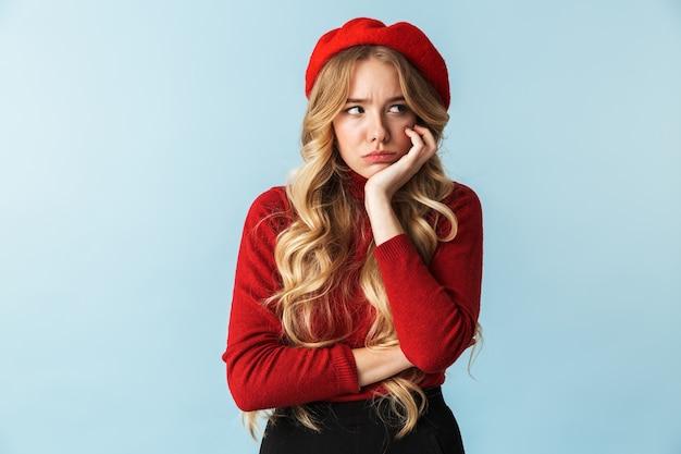 Imagem de uma mulher loira de 20 anos descontente com uma boina vermelha olhando para o lado em pé, isolada