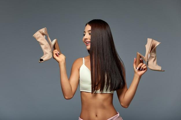 Imagem de uma mulher morena viciada em compras confusa em roupa interior, segurando sapatos novos, mostra emoções.