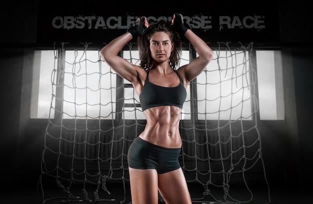 Imagem de uma mulher musculosa malhando na academia.
