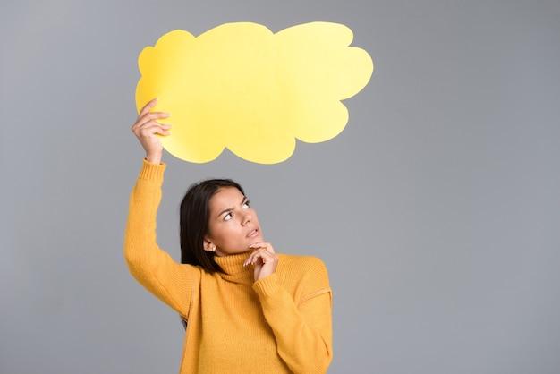 Imagem de uma mulher pensativa posando isolada sobre uma parede cinza segurando o balão de pensamento.