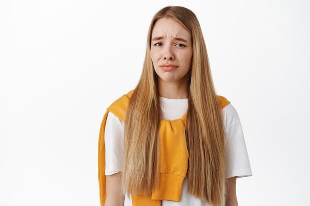 Imagem de uma mulher sentindo-se nojenta ou com pena, fazendo careta de desgosto e nojo, carrancuda e chateada, de pé contra uma parede branca