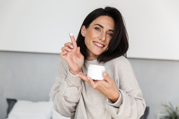 Imagem de uma mulher sorridente, na casa dos 30 anos, segurando um frasco com creme facial, em uma sala moderna e iluminada