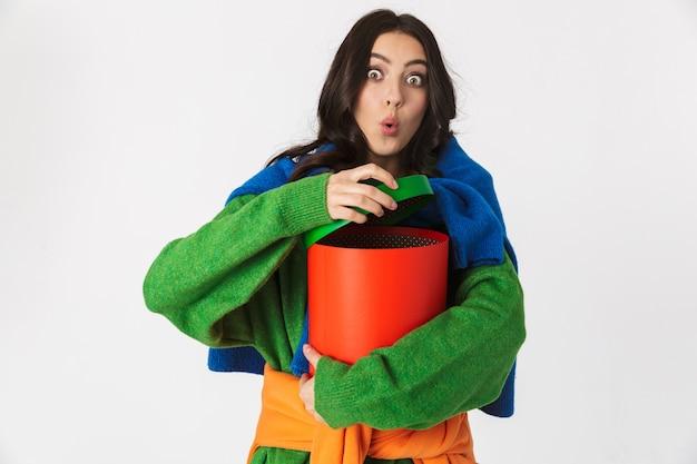 Imagem de uma mulher surpresa com cabelos escuros em roupas coloridas, segurando uma caixa grande para presente em pé, isolada no branco