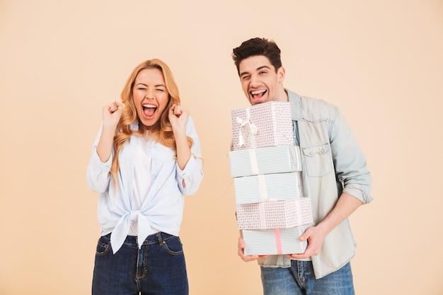 Imagem de uma mulher surpresa gritando de felicidade enquanto um homem bonito segurando várias caixas de presente, isoladas sobre uma parede bege