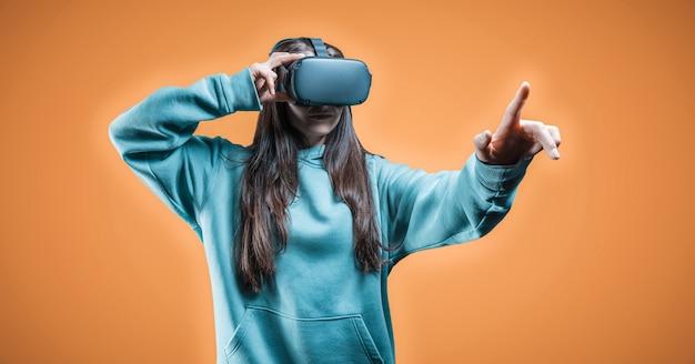 Imagem de uma mulher usando óculos de realidade virtual em um fundo laranja