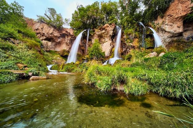 Imagem de uma paisagem verdejante com rio e três cachoeiras caindo sobre falésias