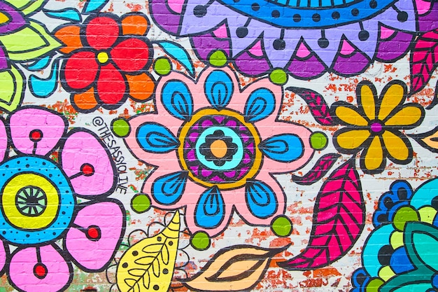 Imagem de uma parede de tijolos coberta por uma arte de flores coloridas