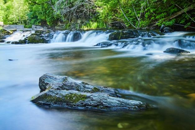 Imagem de uma rocha solitária com musgo em um rio tranquilo com cachoeiras e represa ao fundo