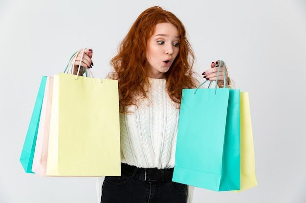 Imagem de uma ruiva linda jovem animado emocional bonito posando isolado sobre o fundo da parede branca, segurando sacolas de compras.