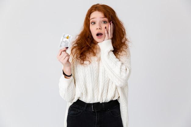 Imagem de uma ruiva linda jovem bonita animado posando isolado sobre o fundo da parede branca, segurando o cartão de crédito.