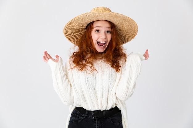 Imagem de uma ruiva linda jovem bonita animado posando isolado sobre o fundo da parede branca usando chapéu.