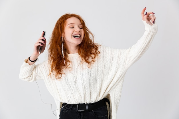 Imagem de uma ruiva linda jovem bonita feliz posando isolado sobre o fundo da parede branca, usando a música do telefone móvel.