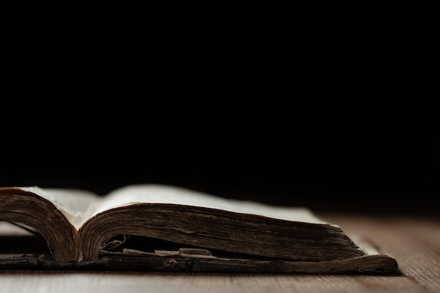 Imagem de uma velha bíblia sagrada em fundo de madeira em um espaço escuro