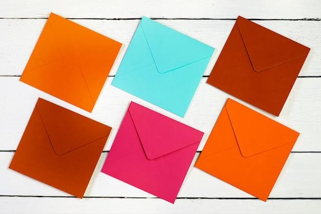 Imagem de uma vista superior de envelopes multicoloridos em uma mesa de madeira branca.