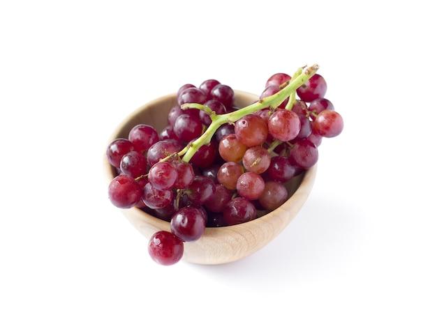 Imagem de uvas vermelhas em uma tigela de madeira, isolada no fundo branco