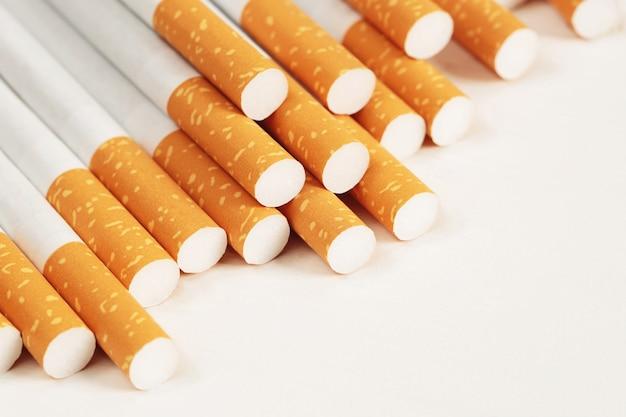 Imagem de vários cigarros de pilha fabricados comercialmente em fundo branco. ou conceito de campanha para não fumantes, vista superior do padrão de tabaco.