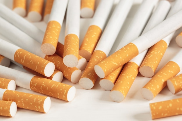 Imagem de vários cigarros de pilha feitos comercialmente em fundo branco. ou conceito de campanha para não fumantes, vista superior do padrão de tabaco.