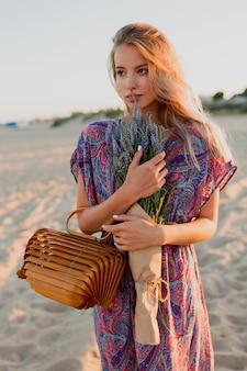 Imagem de verão ao ar livre da bela mulher loira romântica em vestido colorido, caminhando na praia com buquê de lavanda.
