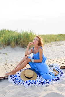 Imagem de verão ao ar livre de mulher romântica relaxante na praia ensolarada com vestido azul.