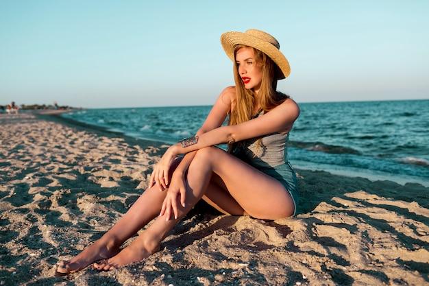 Imagem de verão ao ar livre de uma linda mulher loira com chapéu de palha, caminhando perto do mar.