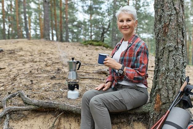 Imagem de verão ao ar livre de uma mulher alegre de meia-idade vestindo roupas esportivas relaxando sob uma árvore com equipamento de acampamento e chaleira no queimador de gás, segurando uma caneca, tomando chá fresco, descansando enquanto caminha sozinho