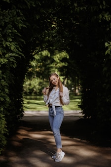 Imagem de verão lindo modelo completo. um corpo esbelto. passeio de verão no parque. espaço verde turva. sorriso e felicidade