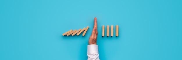 Imagem de visão ampla da mão masculina, parando os dominós de queda. sobre fundo azul.