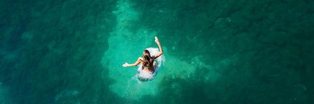 Imagem de visão ampla de uma jovem mulher pulando em um belo lago verde frio.