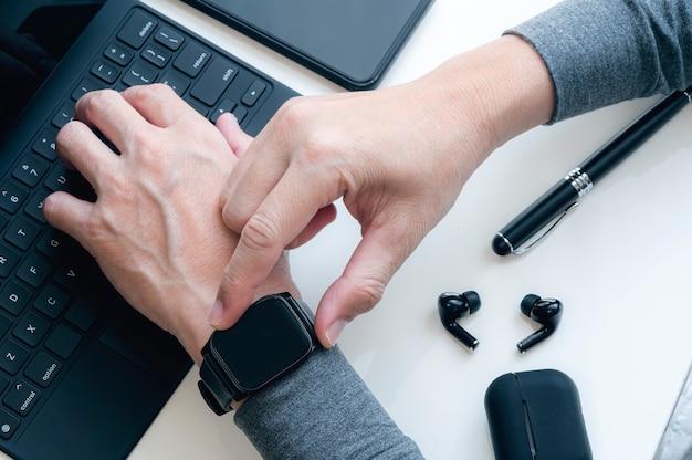Imagem de vista superior da mão do homem usando o smartphone enquanto trabalhava na mesa do escritório.