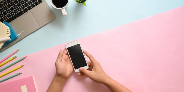 Imagem de vista superior das mãos segurando um smartphone branco recortado com tela em branco preta na mesa com computador portátil, xícara de café, lápis, diário, caderno e planta em vaso. conceito de local de trabalho em ordem.