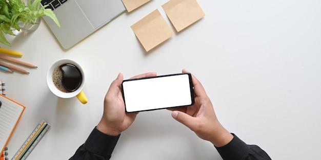 Imagem de vista superior das mãos segurando um smartphone preto cortado com tela em branco branca na mesa branca com computador portátil, xícara de café, lápis, diário, caderno e planta em vaso, régua, postá-lo.