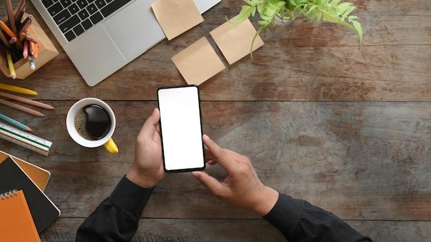 Imagem de vista superior das mãos segurando um smartphone preto recortado com tela em branco branca na mesa de madeira com computador laptop, xícara de café, lápis, diário, caderno e planta em vaso, régua, post-it.