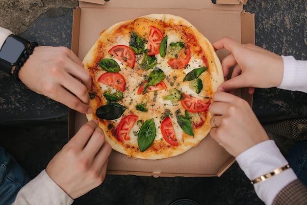 Imagem de vista superior de casal pegando fatias de pizza da caixa ao ar livre