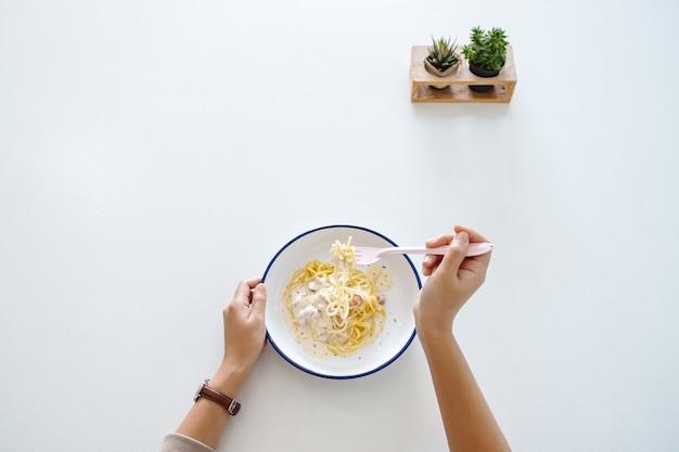 Imagem de vista superior de uma mulher comendo espaguete carbonara na mesa